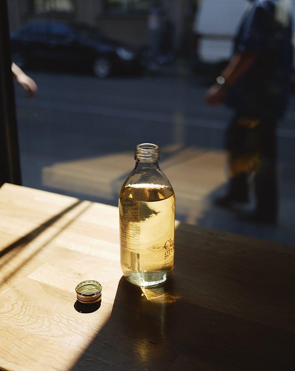 A bottle of tea brew on a table by the street. Berlin