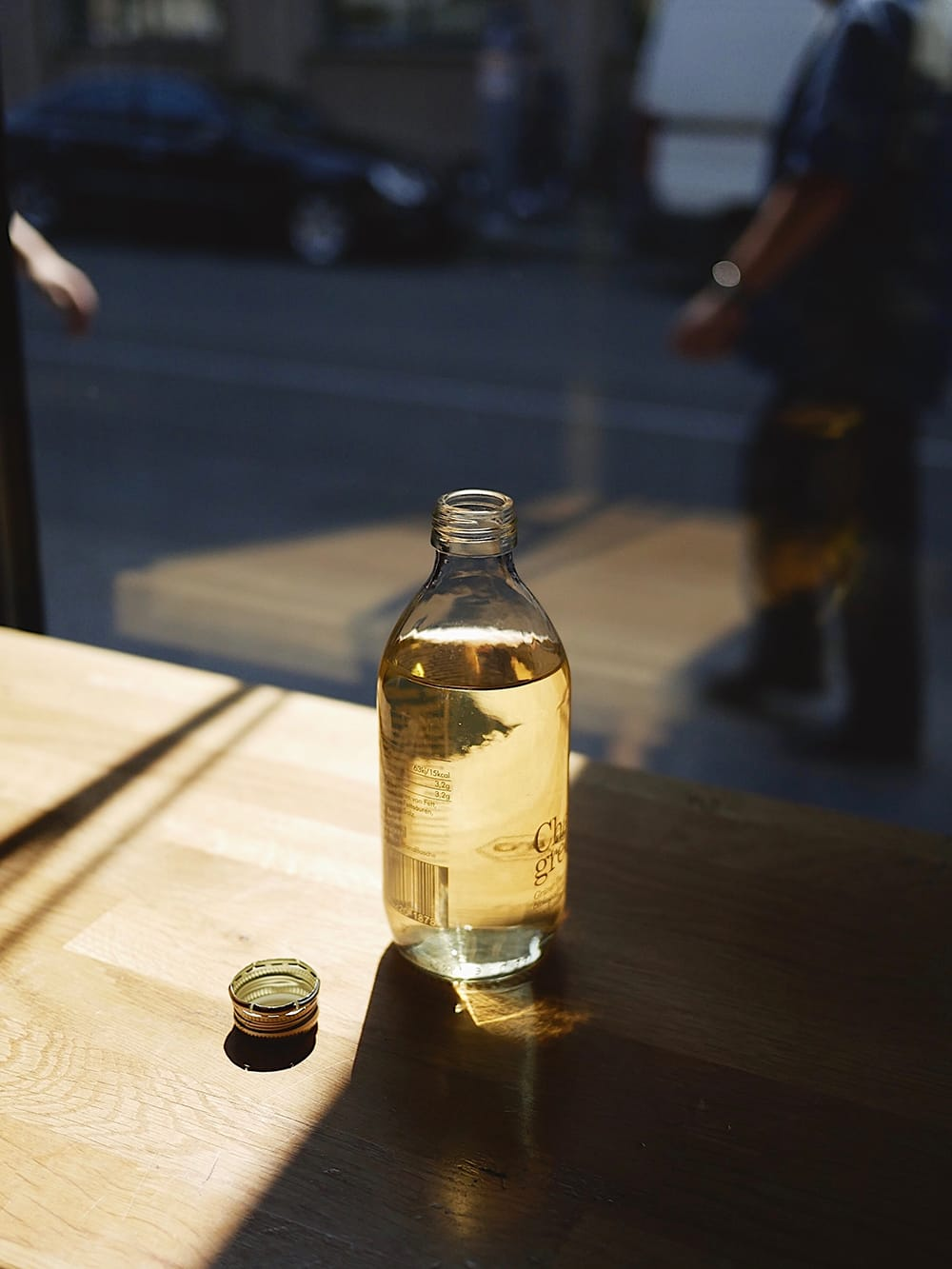 A bottle of tea brew placed on a table by the window in a cafe. Berlin