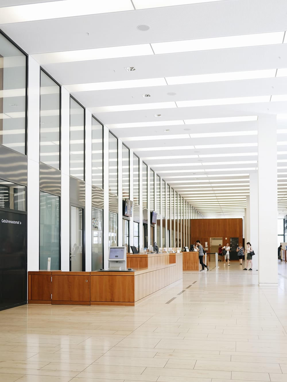 A spacious hall of library with some people in the distance. Berlin