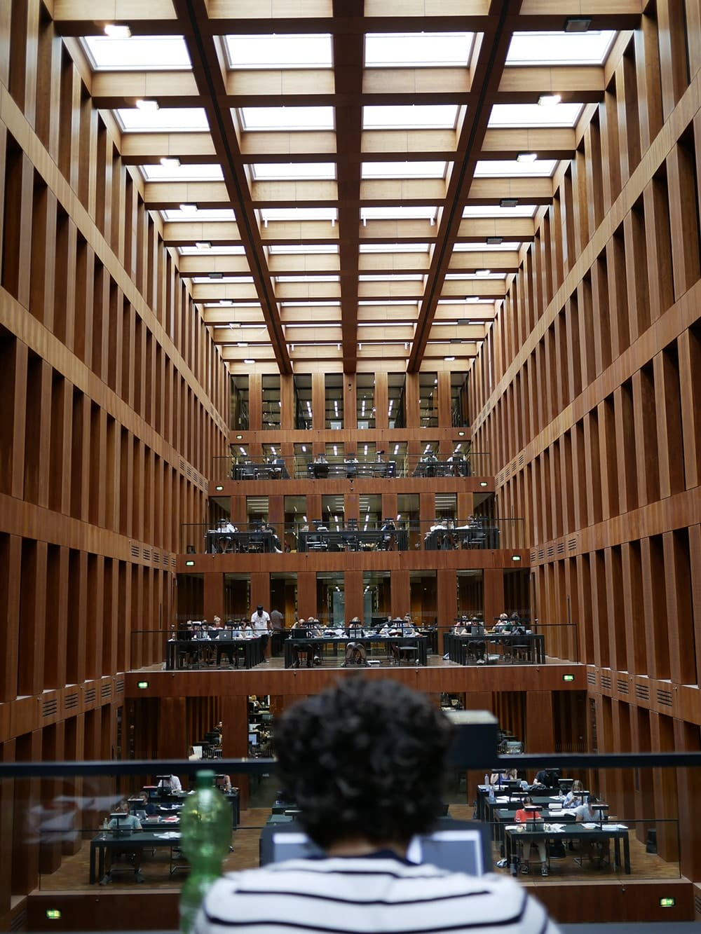 Spacious interior of a library with a reading room covered by glass roof. Berlin
