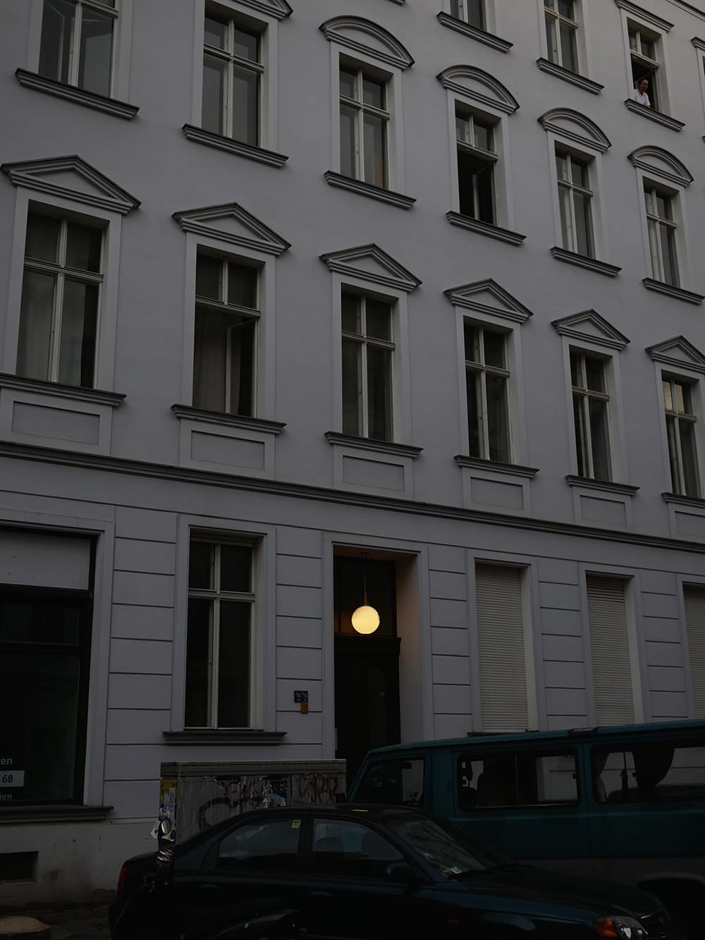 Grey tenement with an entrance illuminated with glass ball. Berlin