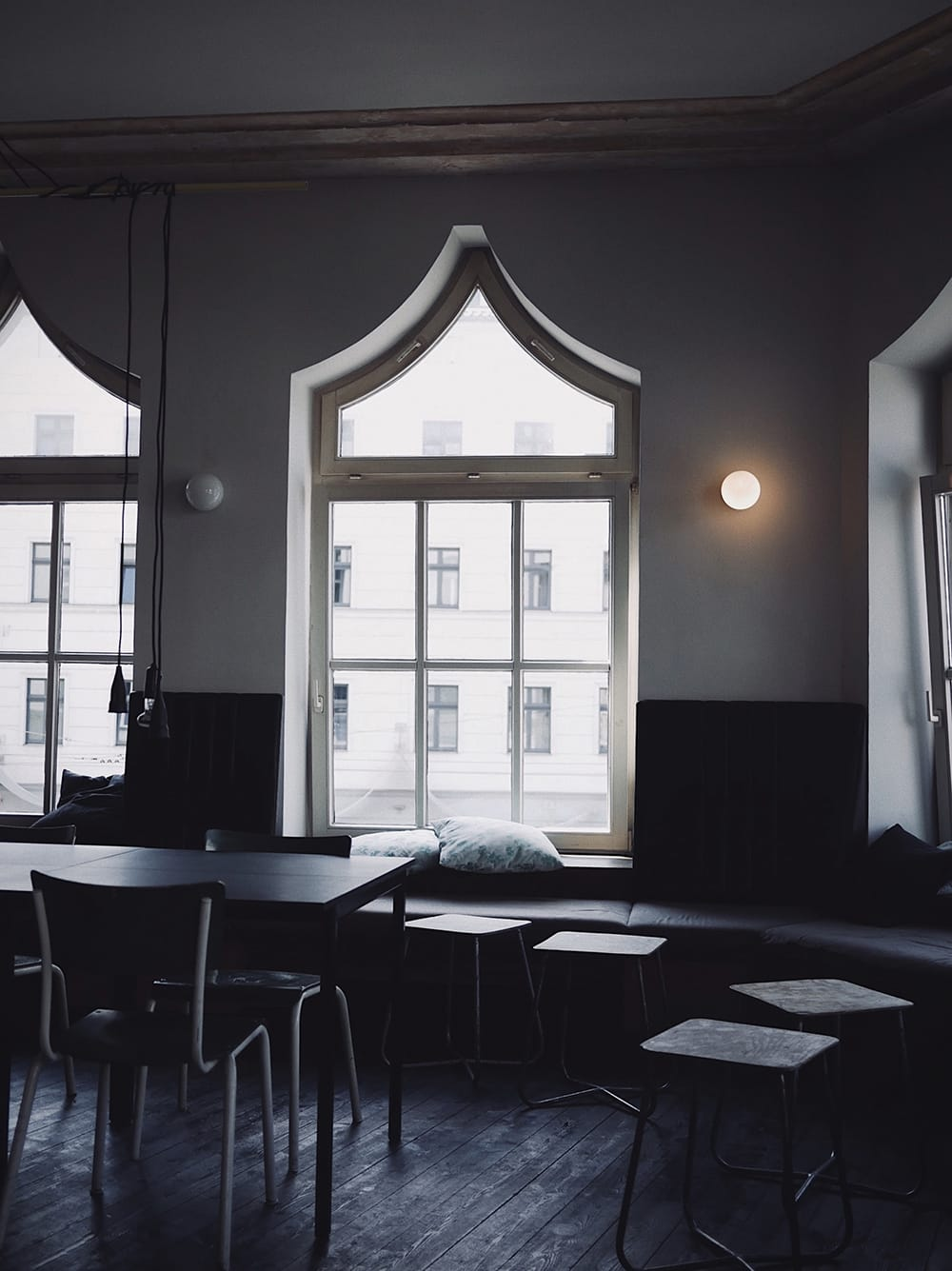 Empty interior of a cafe with big windows up to the ceiling and black furniture. Berlin