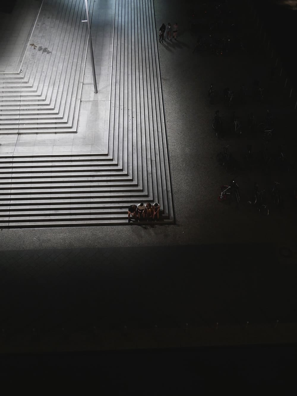 A group of young people sitting together on stairs in warm evening. Berlin