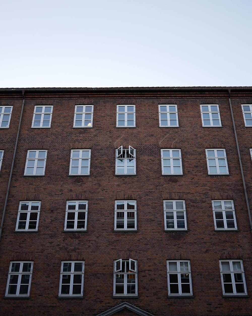 Old, classic tenement with one, opened window in the middle. Copenhagen