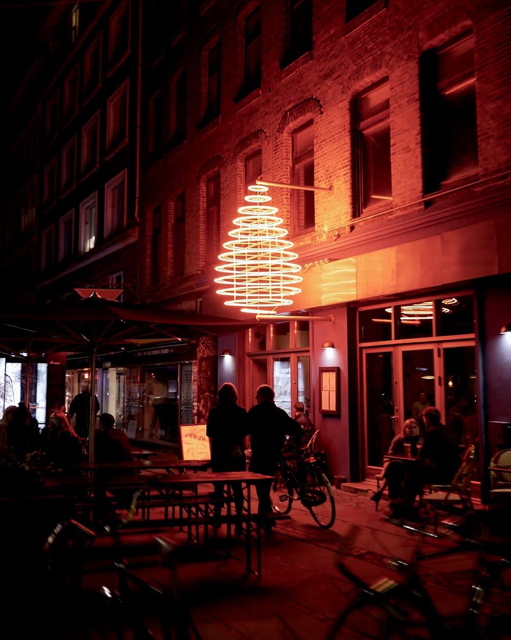 Big, neon light in the shape of drop hang above passersby. Copenhagen