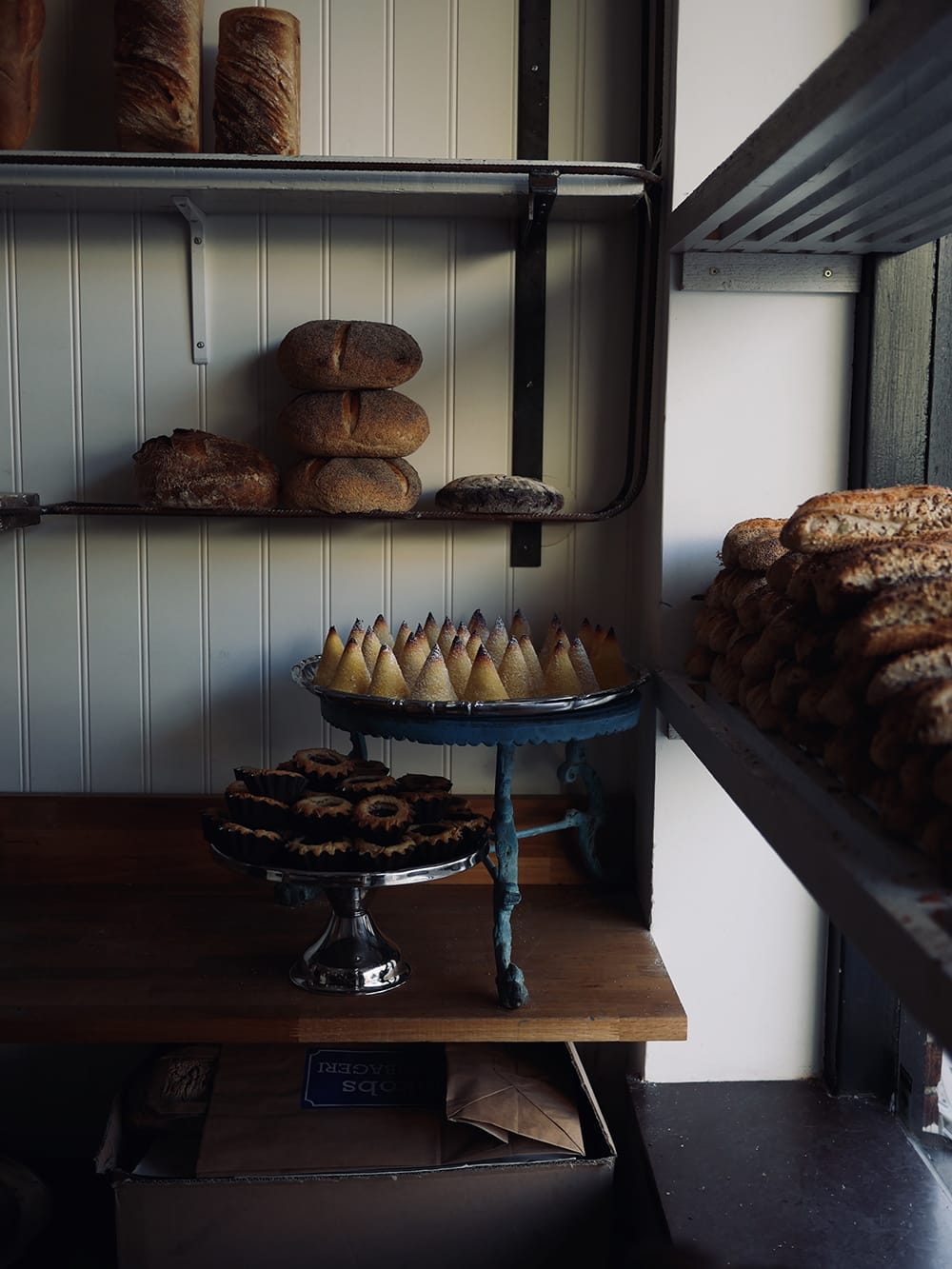 A shaded interior of bakery with a bread and cookies placed on trays and shelves. Malmö