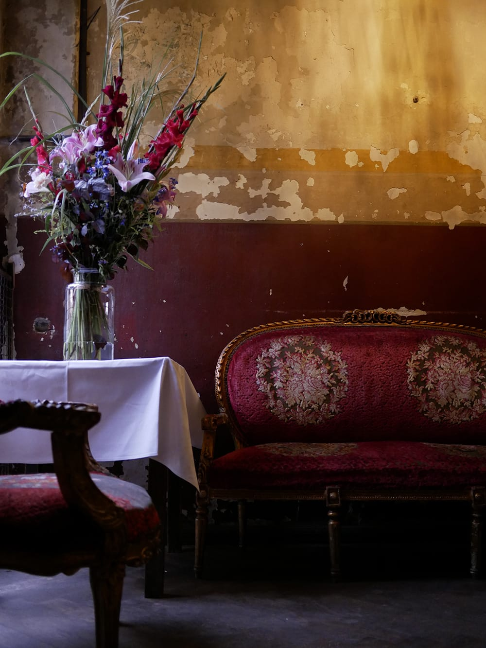 Old, vintage interior of a entryway to ballroom with classy bench and big bouquet of flowers. Berlin, Germany