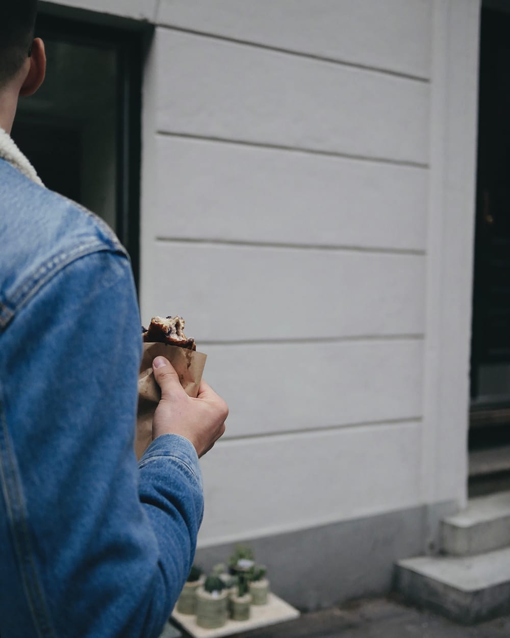 A young man eating sweet chocolate bun on the street. Copenhagen