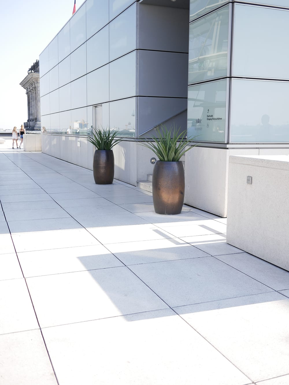 A sunny roof of a museum with two big flowerpots in front of glass facade. Berlin