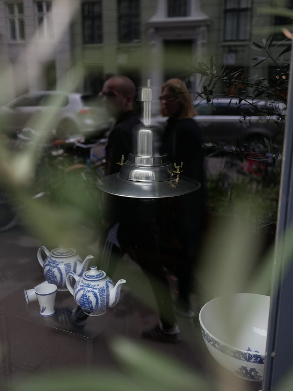 A pair of passersby reflecting at shop window with industrial lamp. Copenhagen