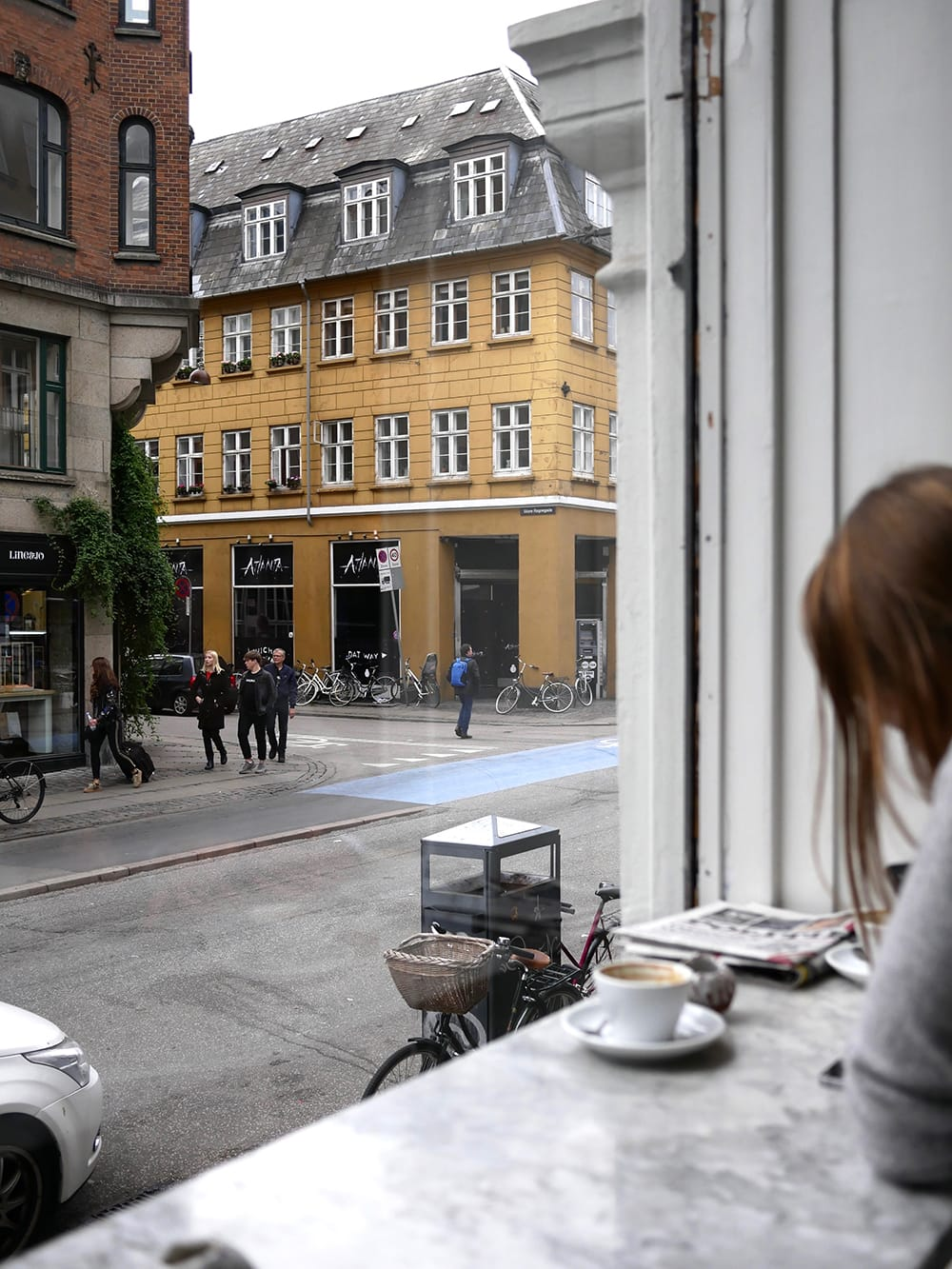 Interior of a bright cafe with big window and view on a street. Copenhagen