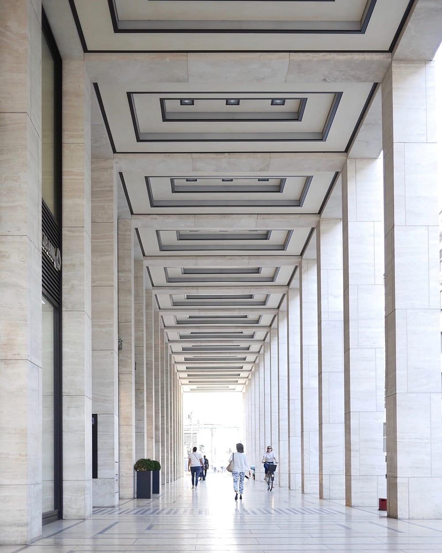 Passersby walking under arcade with pillars. Berlin