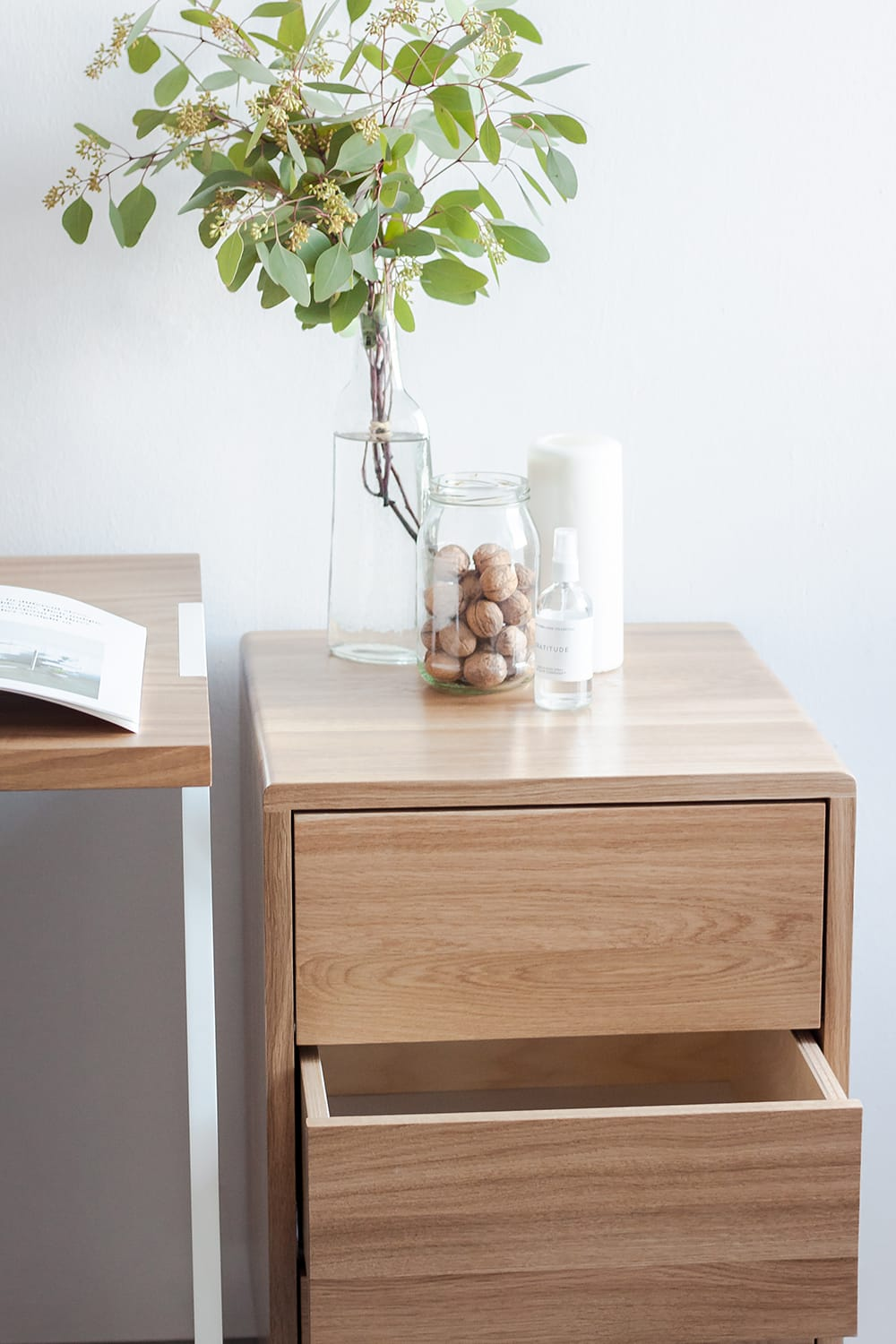 Minimalistic, wooden cabinet with a vase, flowers and candle on it. It is in a white studio. borcas brand