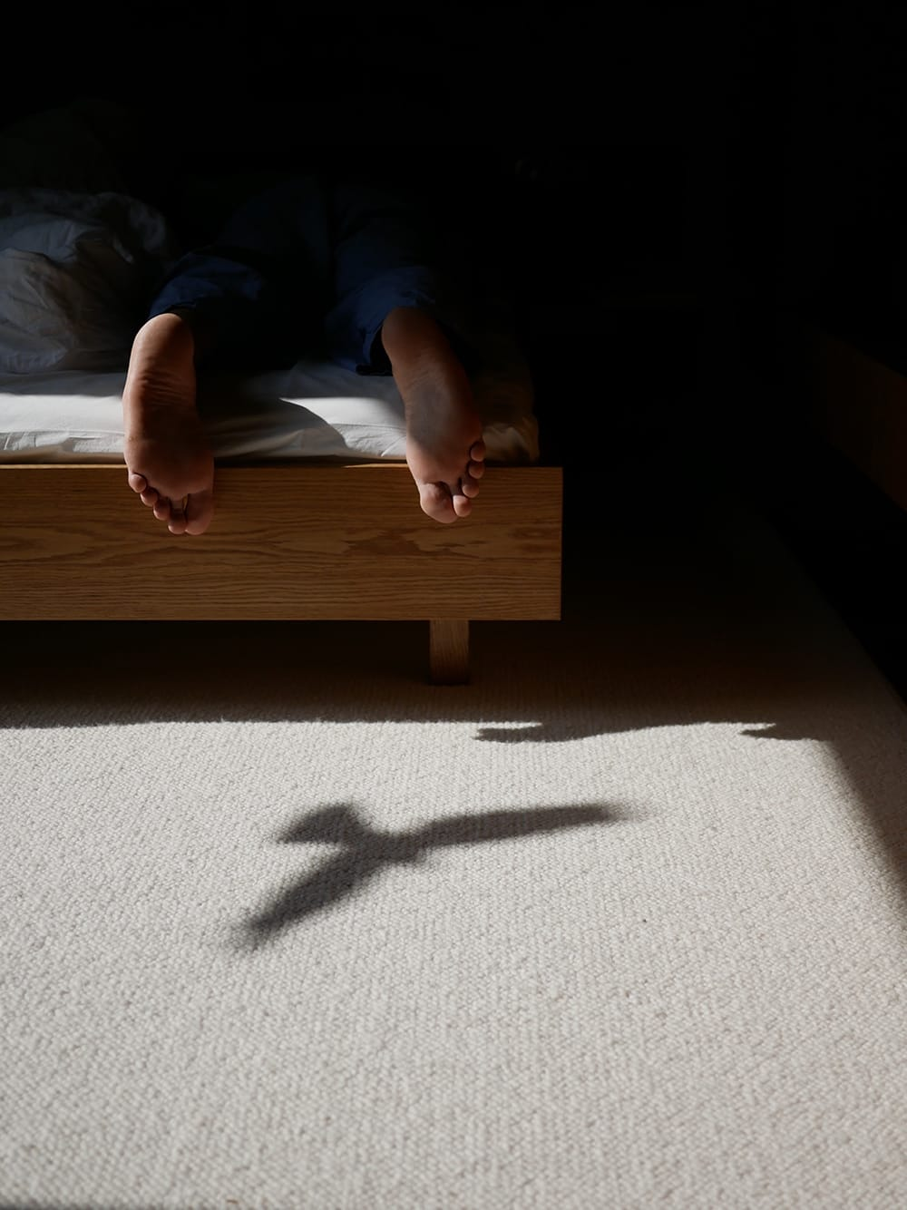 Men feet on a bed with a bird shadow next to them.