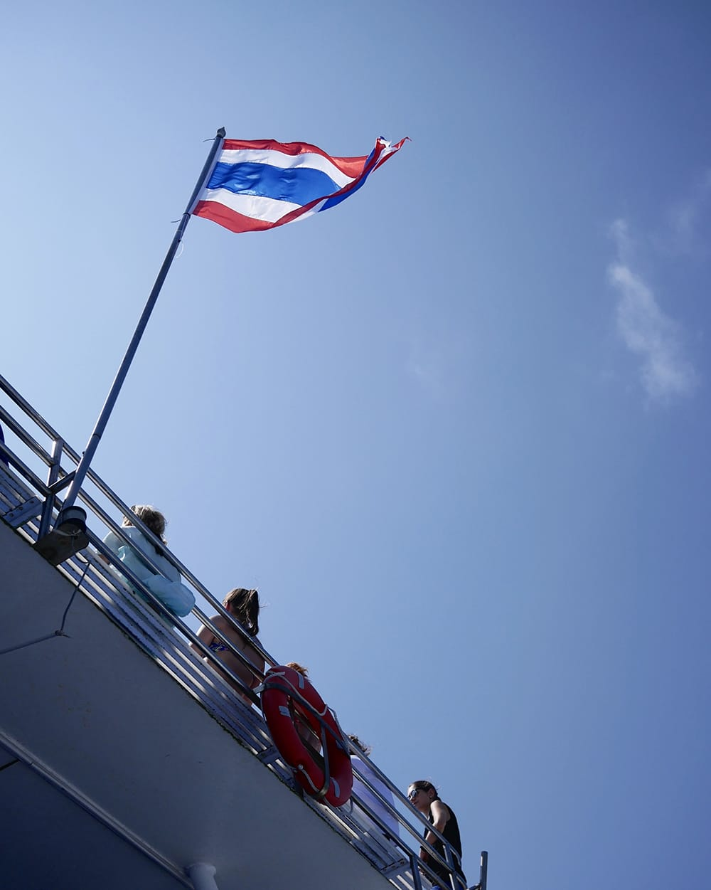 A few people sitting backwards on a deck of ferry with a Thai flag behind them. Koh Phi Phi