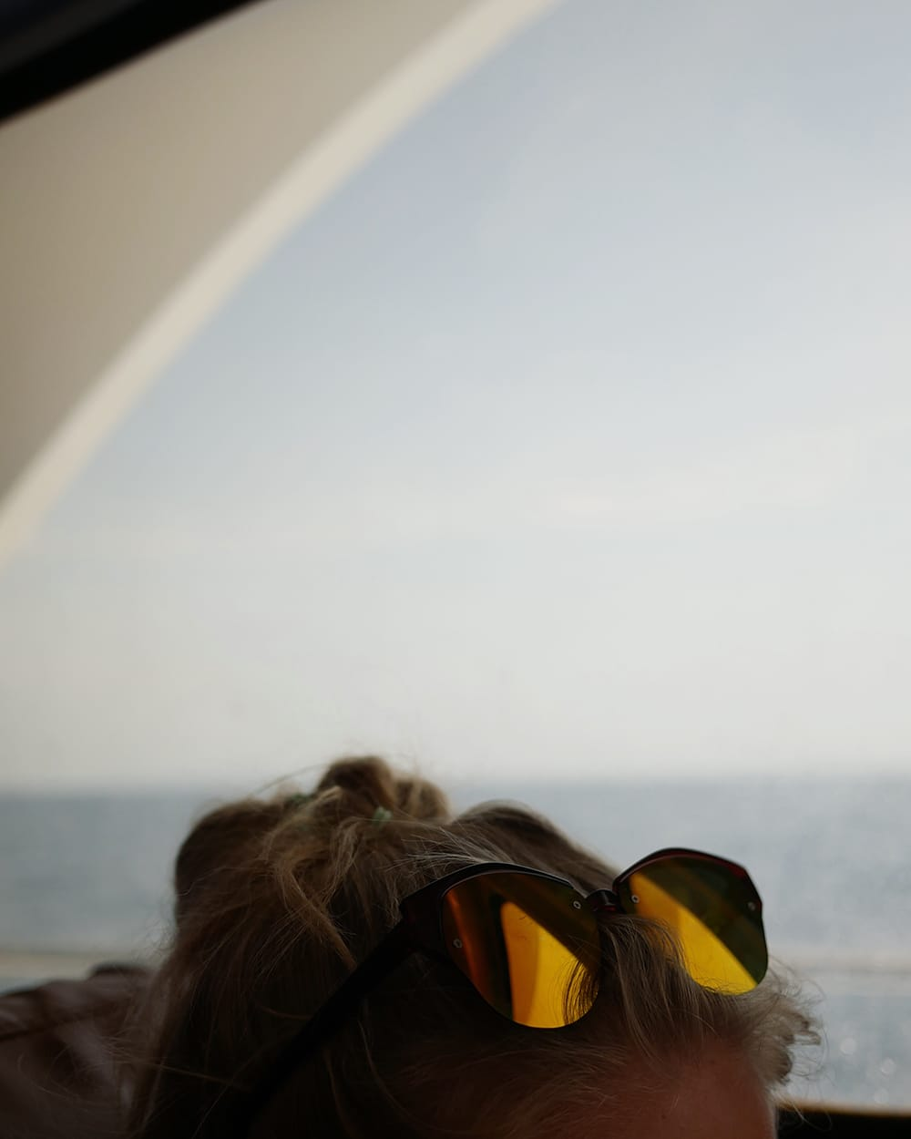 A woman sitting on a ferry and wearing pair of sunglasses on a head. Koh Phi Phi