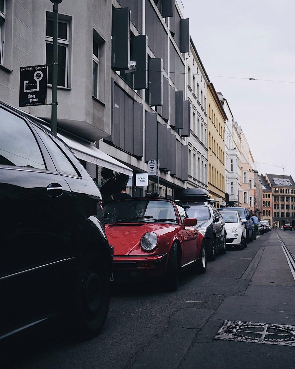 Red vintage Porsche car hidden behind other cars. Berlin