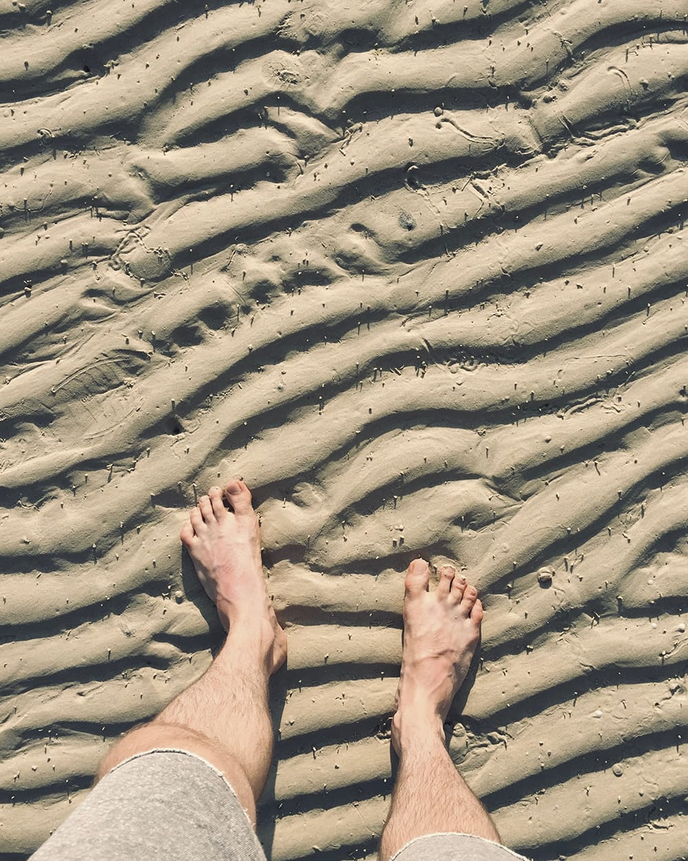 Men feet on a wavy pattern of sand. Koh Phi Phi