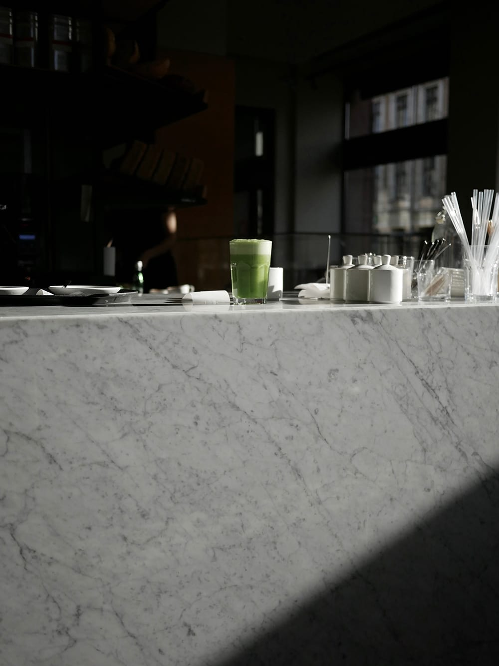 A glass of green cocktail placed on a shaded, marble bar. Wroclaw