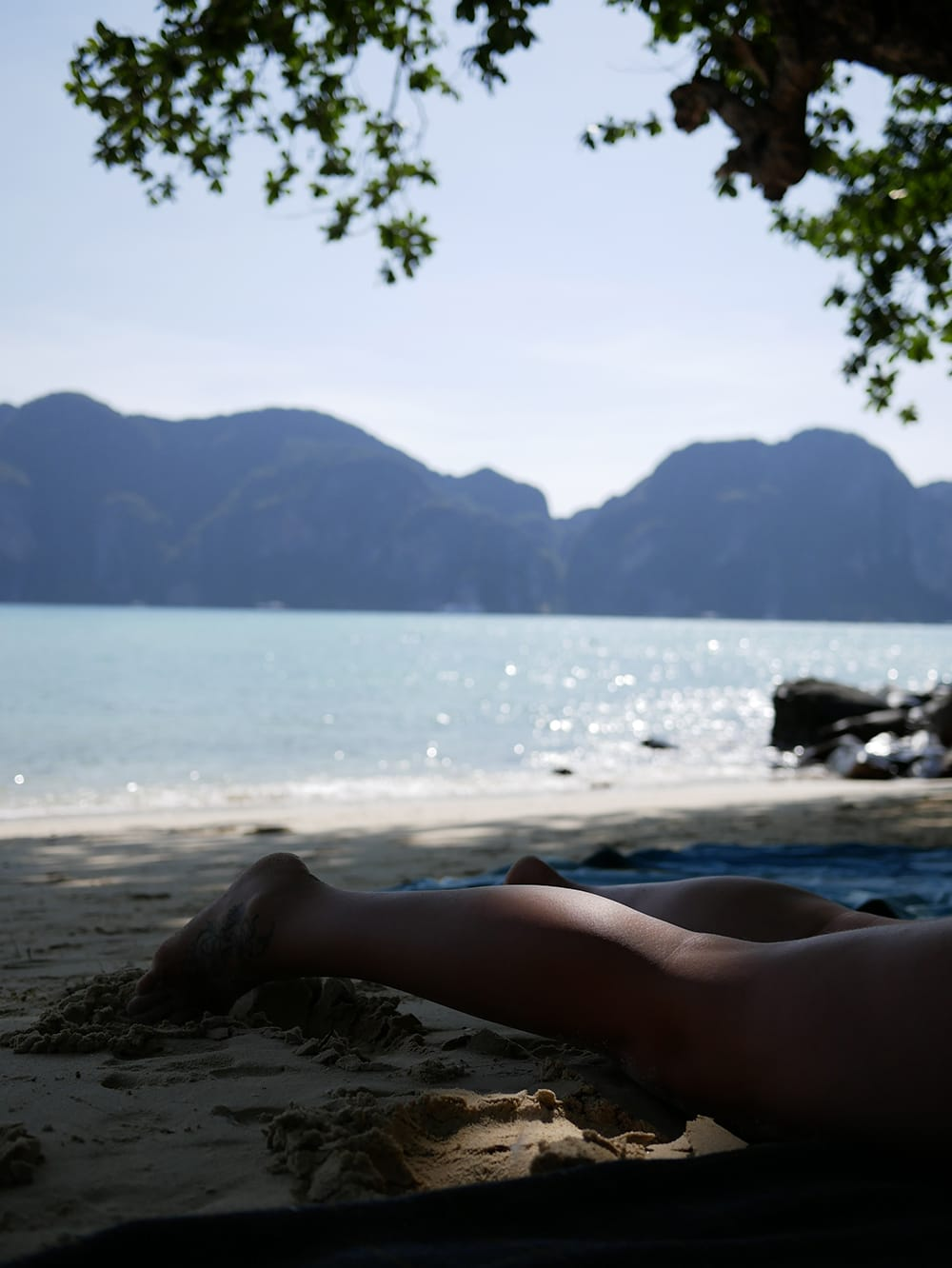 Women legs on a shaded beach. Koh Phi Phi