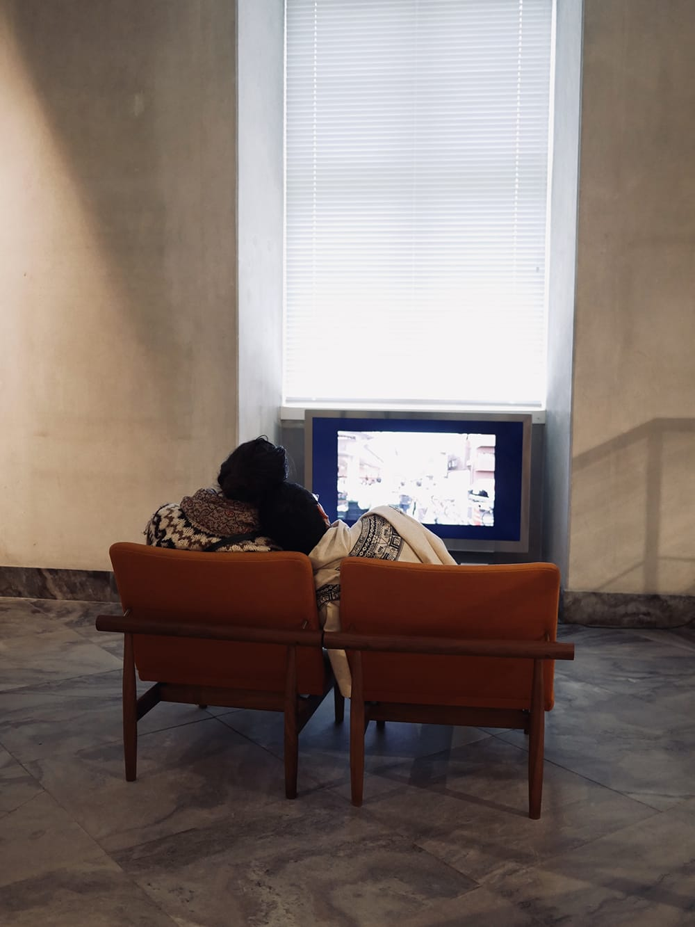 Two visitors of a museum cuddling up in front of television. Copenhagen