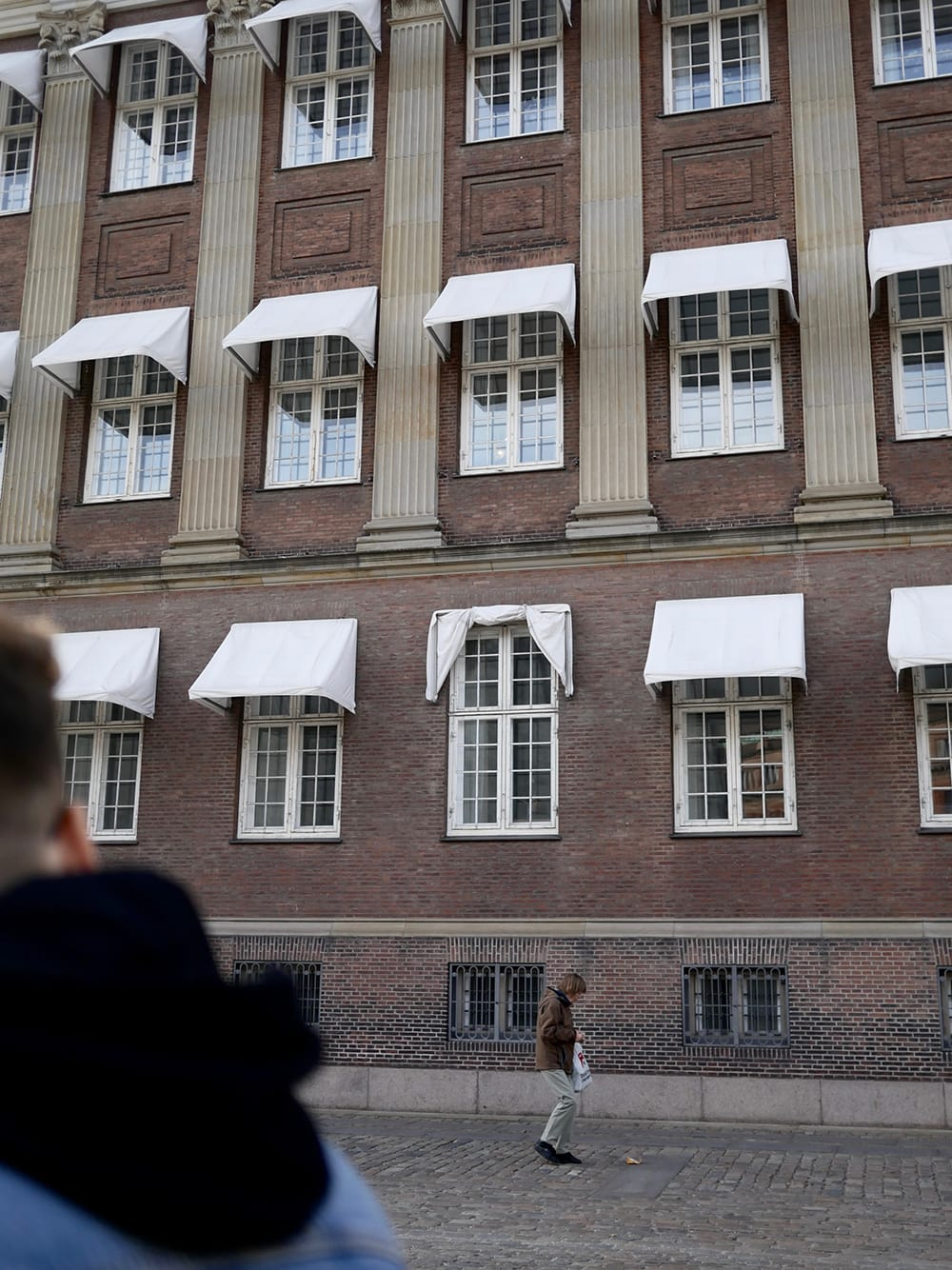 Old tenement with classic, white canopies and passerby in front of it. Copenhagen