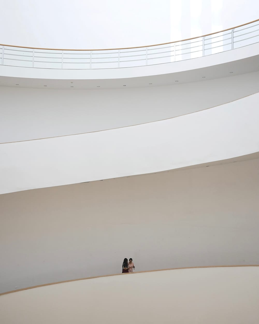 Interior of a spacious staircase in design museum with two visitors in the middle. Bangkok, Thailand