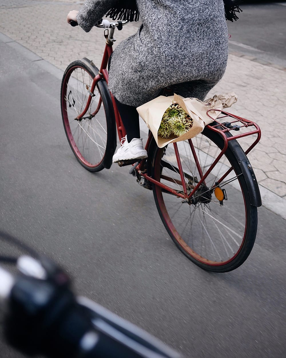 A bike rider with a bouquet of flowers on the trunk. Copenhagen
