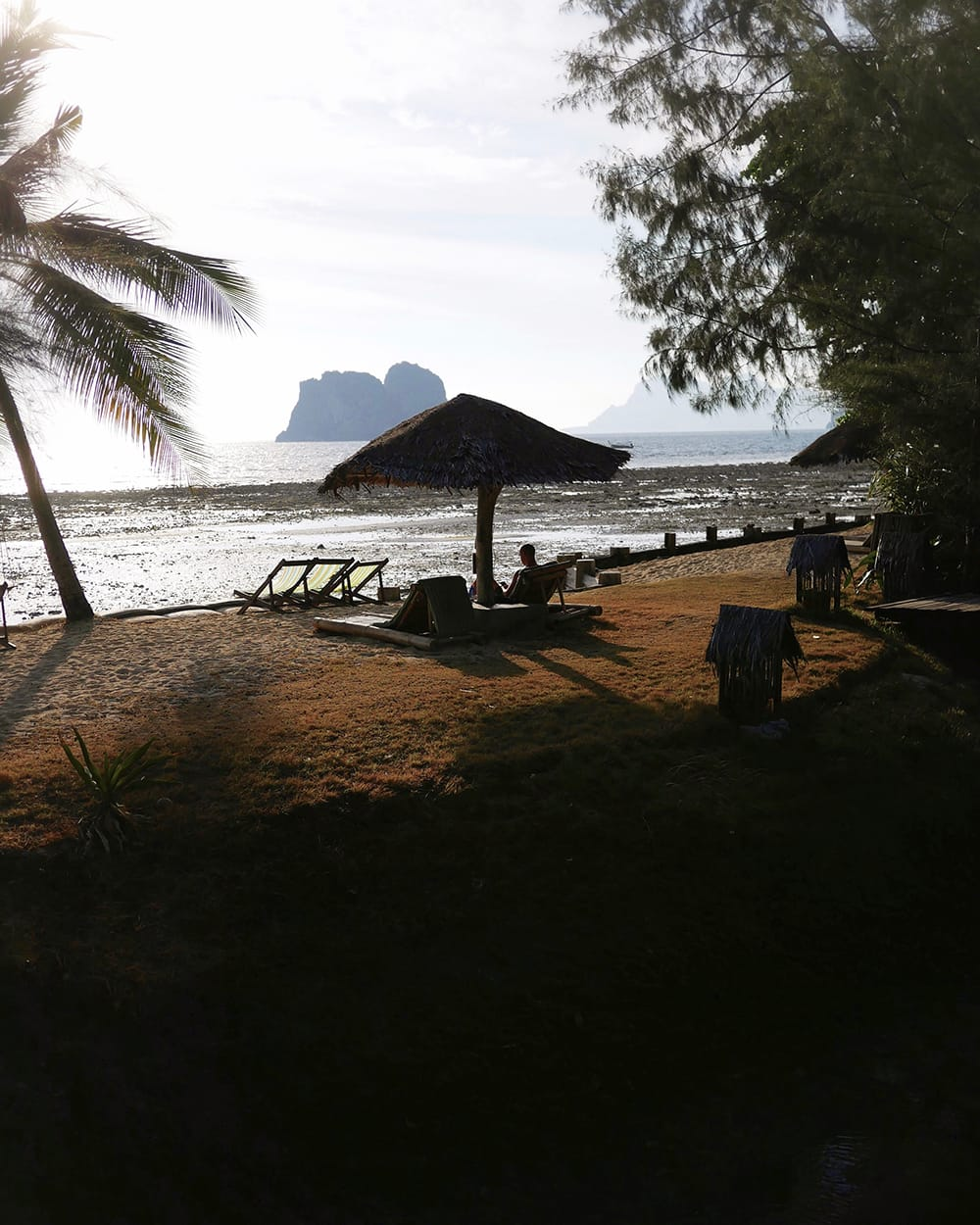 A man laying on a beach, under an umbrella during sunset. Koh Ngai