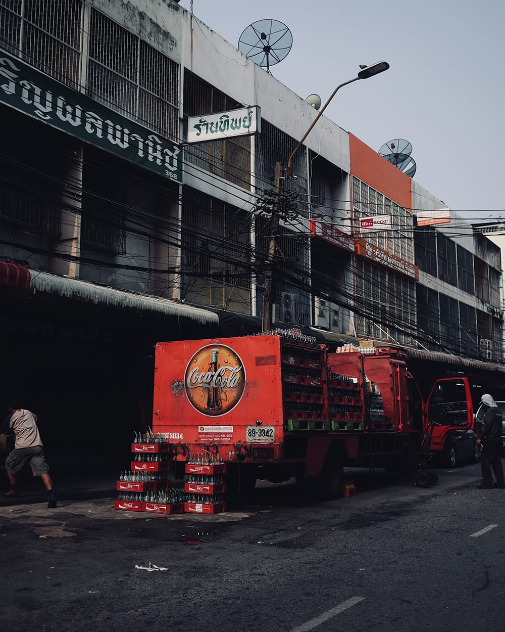 Red truck with coke parked in a dirty neighborhood. Bangkok