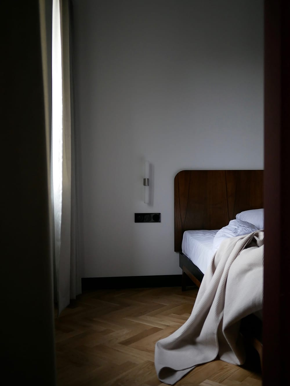Interior of dark, shaded bedroom with unmade bed. Gdansk, Poland