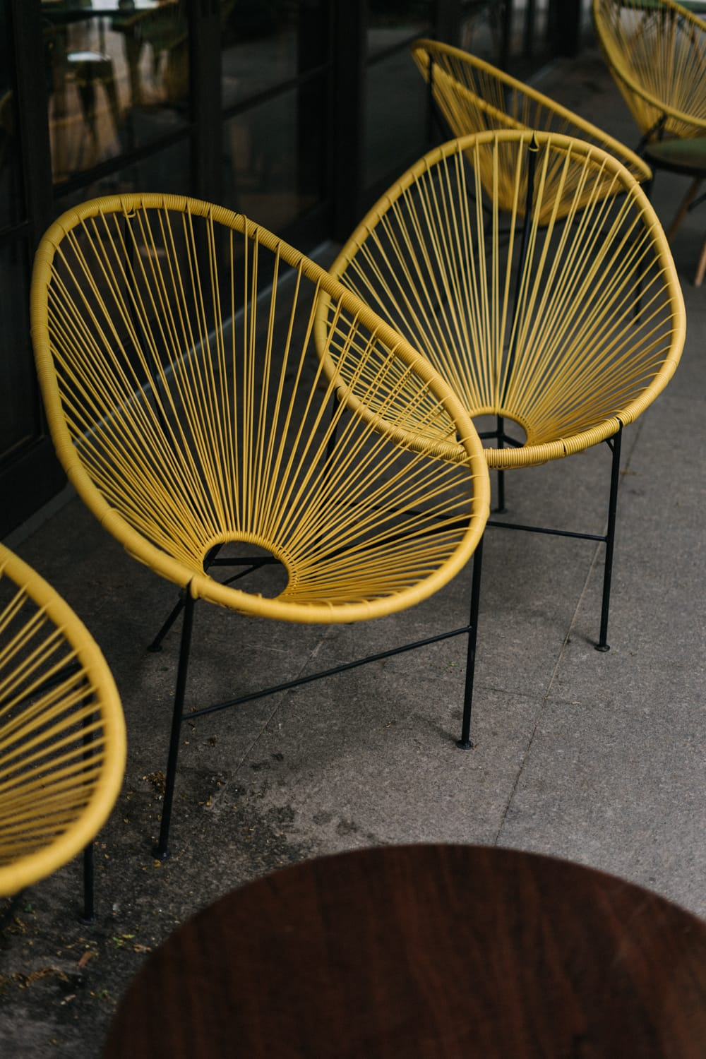 Yellow, big outdoor armchairs placed in a cafe garden. Warsaw